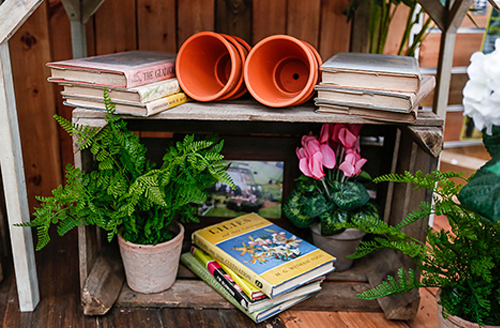 A stack of gardening books sit next to some potted plants